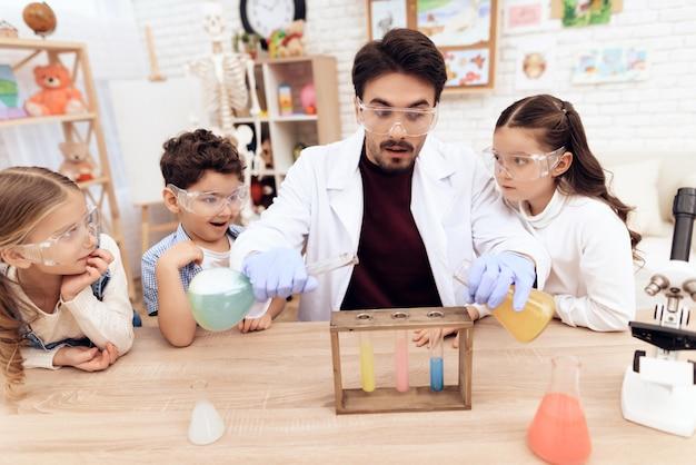Дети вместе с учительницей на уроках химии. Premium Фотографии