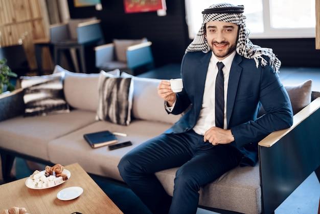 アラブのビジネスマンがホテルの部屋でソファでコーヒーを飲みます。 Premium写真