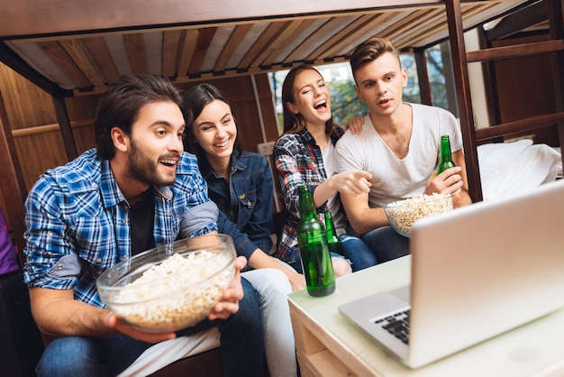 男の子と女の子はポップコーンとラップトップで映画を見ています。 Premium写真