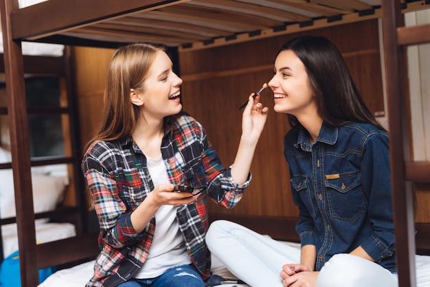 微笑んでいる女の子はベッドの上に座るし、ガールフレンドを描画します。 Premium写真