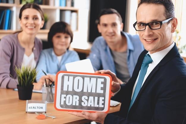 全米リアルター協会加入者は、家族と一緒に販売サインのための家を提示しています。 Premium写真