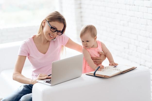 赤ちゃんの作業とラップトップを使用して若い母親。 Premium写真