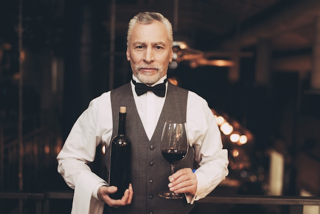 ソムリエはガラスと瓶でワインを持っています。 Premium写真