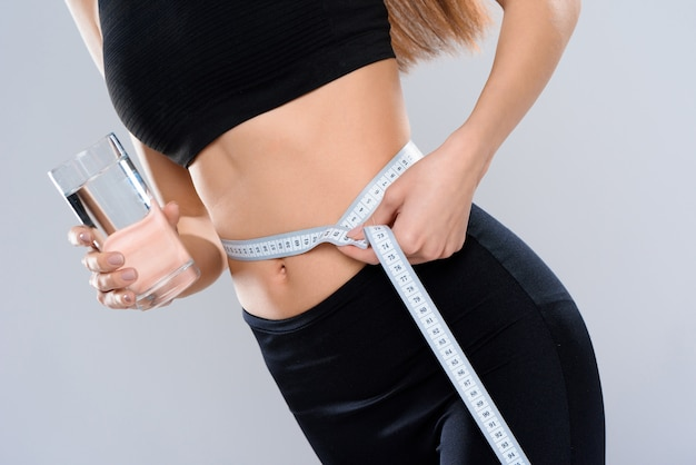 閉じる。女の子はセンチメートルで腰を測定します。 Premium写真
