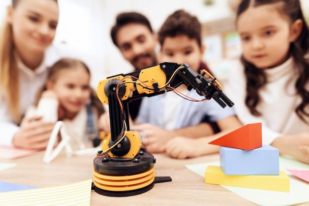 Дети смотрят на робота. Premium Фотографии