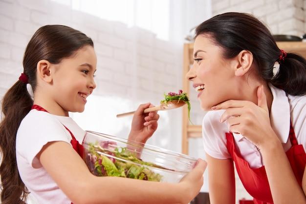 小さな娘は台所で母に餌をやる。 Premium写真