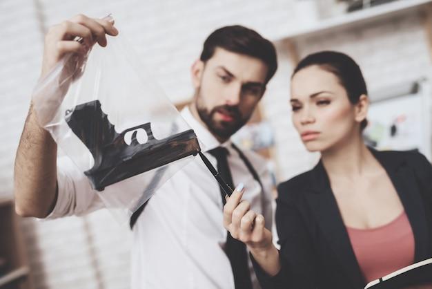 女性が書いている間証拠として銃を保持している男。 Premium写真