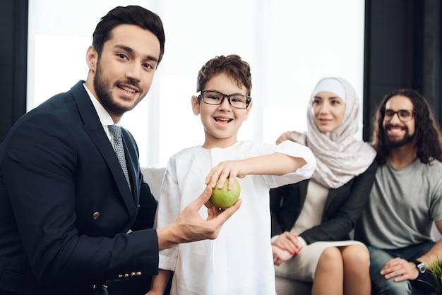 少年は心理療法士と笑顔からアップルを取ります。 Premium写真