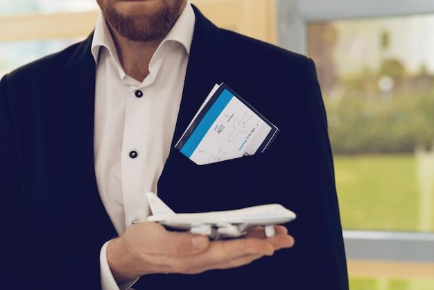 黒のスーツを着た男のクローズアップ写真は航空機を保持します。 Premium写真