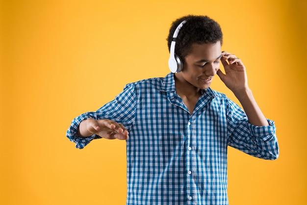 ヘッドフォンでアフロティーンエイジャーが踊っています。 Premium写真