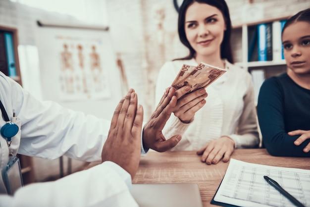 女性は診療所で医者を買収しようとします。 Premium写真