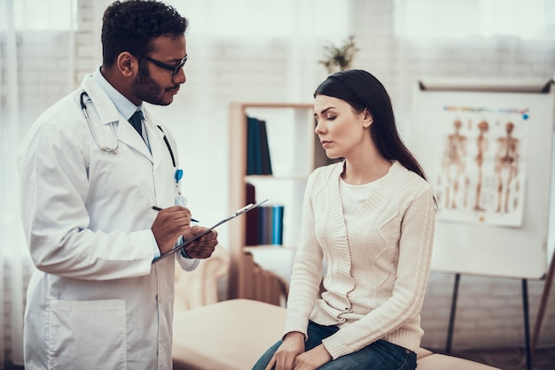 医者は女性の症状を聞いています。 Premium写真