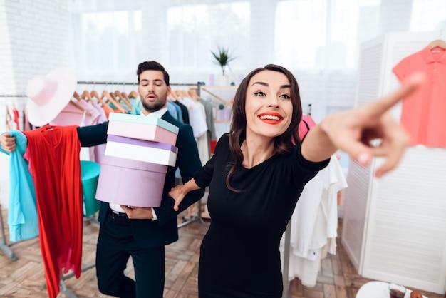 彼女が見せている間、男は彼のガールフレンドのために買い物をしています。 Premium写真