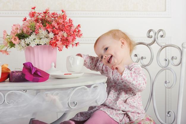 お茶と装飾、肖像画、クローズアップでテーブルに座っている少女 Premium写真