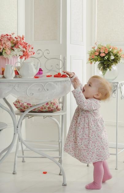 内部のお茶のためのテーブルの近くのドレスの少女 Premium写真