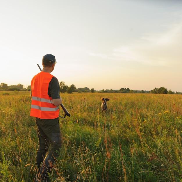 Охотник осенью охотничий сезон со своей охотничьей собакой на закате. Premium Фотографии