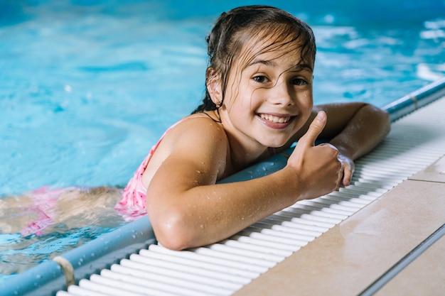屋内プールで楽しんでいる少女の肖像画。女の子はウォーターパークで休んでいます。 Premium写真