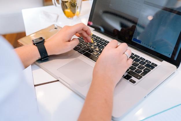 コワーキングオフィスで座っていると彼女のラップトップのキーボードコンピューターに入力するビジネス女性の手を閉じる。 Premium写真
