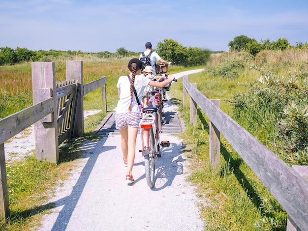 シエルモニコーフ島の砂丘地域の道路を走行する背面のサイクリスト家族。 Premium写真