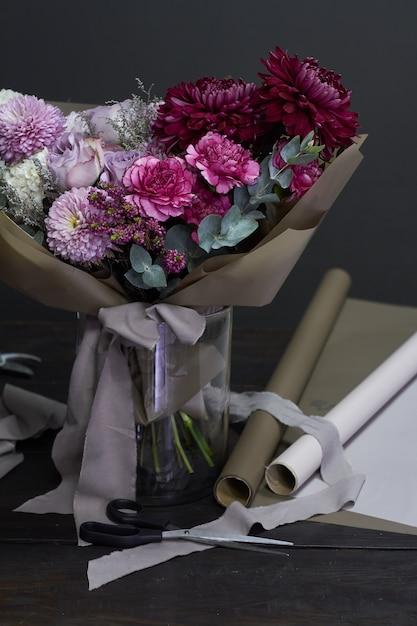 暗闇の中でビンテージスタイルの花屋デスクトップと紫のトーンの花束 Premium写真