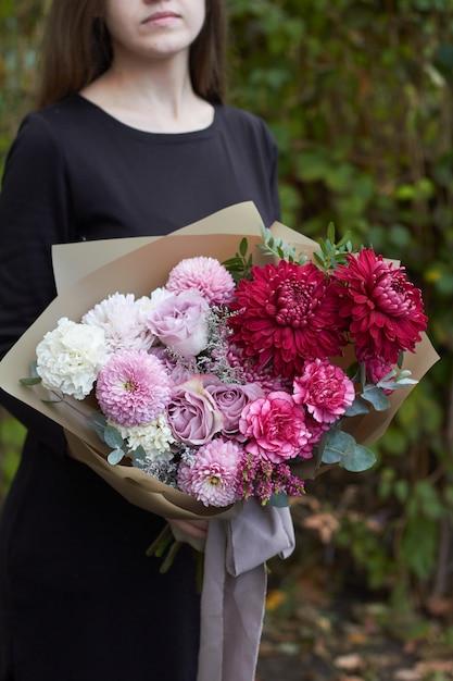 女の子は公園の反対側屋外ビンテージスタイルでピンクと紫のトーンの花束を保持しています Premium写真