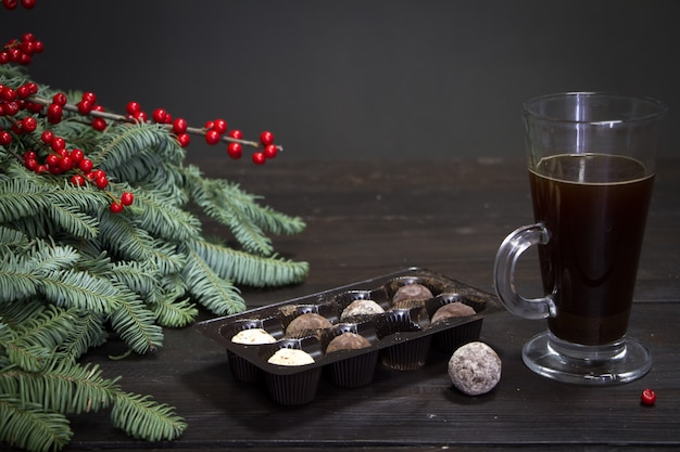 ガラスのコーヒーカップ、チョコレート菓子、クリスマスツリーの枝と赤い果実 Premium写真