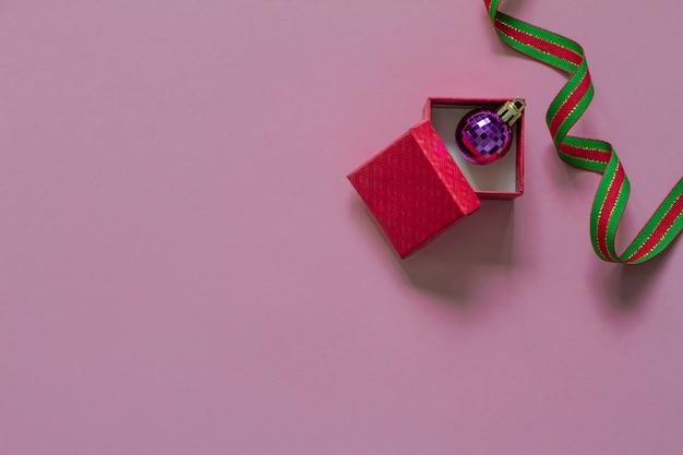 Открытая красная подарочная коробка и фиолетовый рождественский пузырь внутри Premium Фотографии