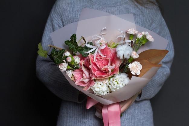 女の子は彼女の手でビンテージスタイル、背景や概念の挨拶で元の花束を保持します Premium写真