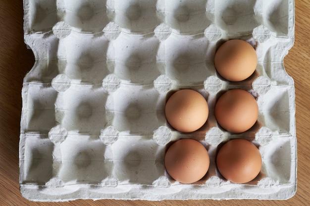 Коричневые яйца крупным планом, куриные яйца в картонный лоток на деревянный стол Premium Фотографии