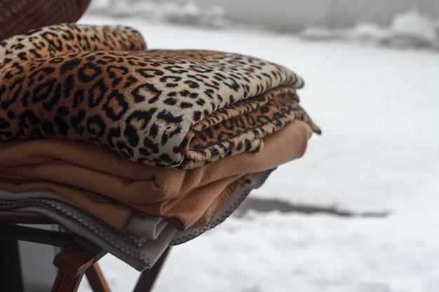 雪に覆われた風景の上の外の椅子に横になっている色とりどりの毛布のスタックのクローズアップ Premium写真