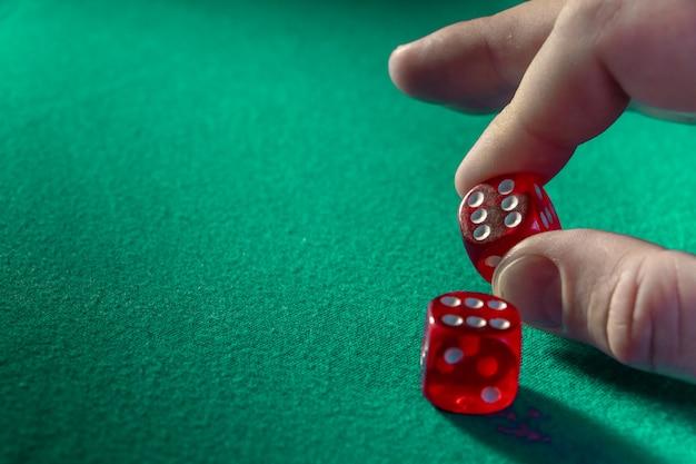 カジノの緑の布の上の勝利の組み合わせで赤いサイコロを持っている手のクローズアップ。 Premium写真