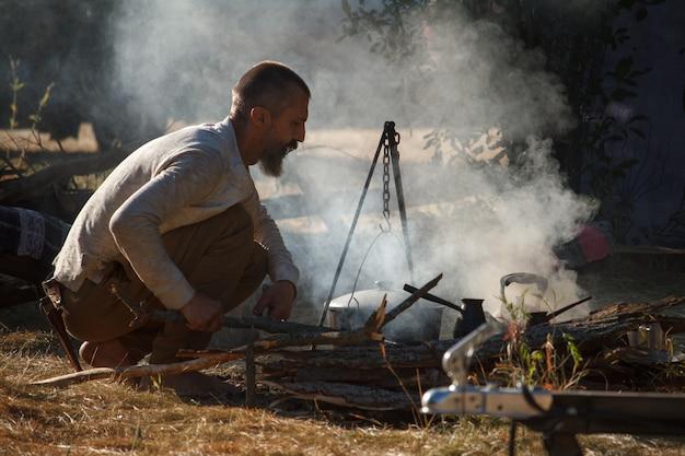 ひげを持つ裸足の男は、調理を開始するために大釜の下で火を作ります Premium写真