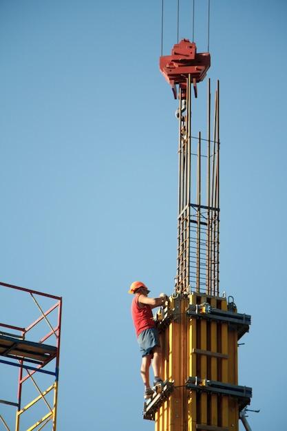 青い空を背景にビルディングブロックを組み立てるとき、建設労働者はクレーンの動きを制御します Premium写真