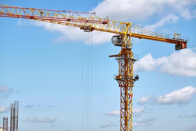 高層ビルの建設、青い空を背景にタワークレーンの操作、選択と集中 Premium写真