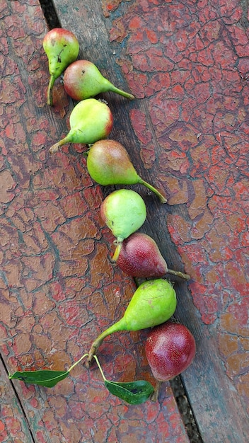 熟した赤緑梨のクローズアップ行は古いベンチにあります。 Premium写真