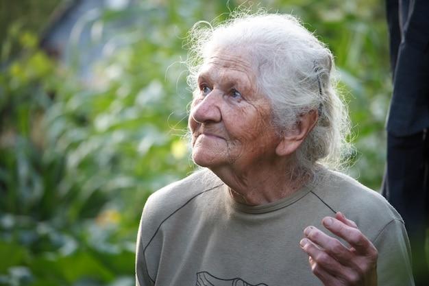 深いしわの顔笑顔と見上げる白髪の老婦人のクローズアップの肖像画 Premium写真