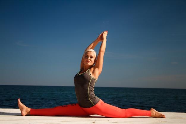 短い髪の大人の金髪の女性は、海と青空を背景に桟橋でヨガを練習します Premium写真