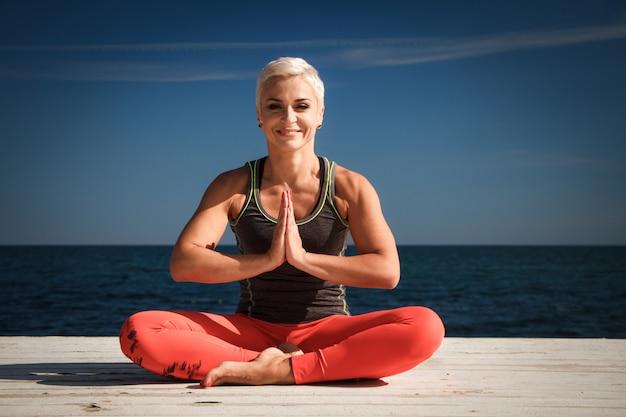 短い散髪と大人の金髪女性のクローズアップの肖像画は、海と青空を背景に桟橋でヨガを実践します。 Premium写真