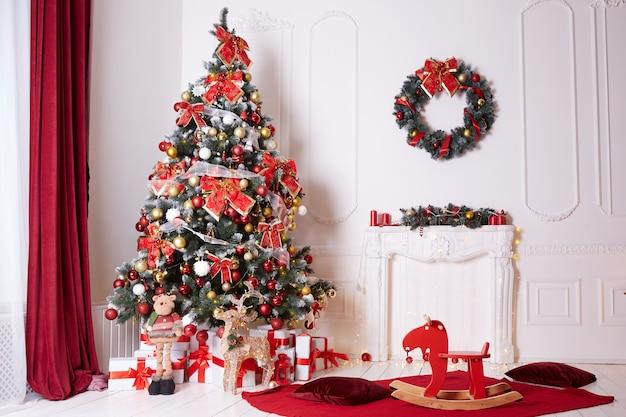 屋内で弓とボールで飾られた美しいクリスマスツリー。 Premium写真