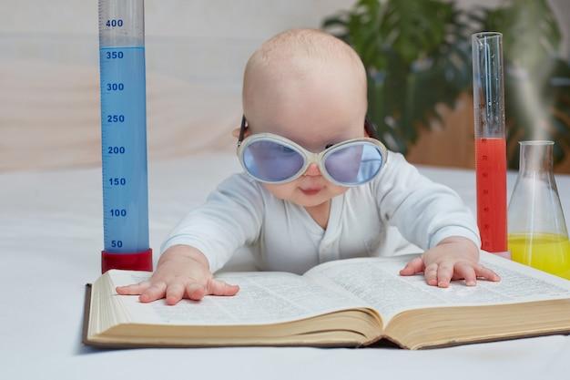Обучение и домашнее обучение. милый малыш читает книгу по медицине, науке, химическим экспериментам. горизонтальное изображение Premium Фотографии
