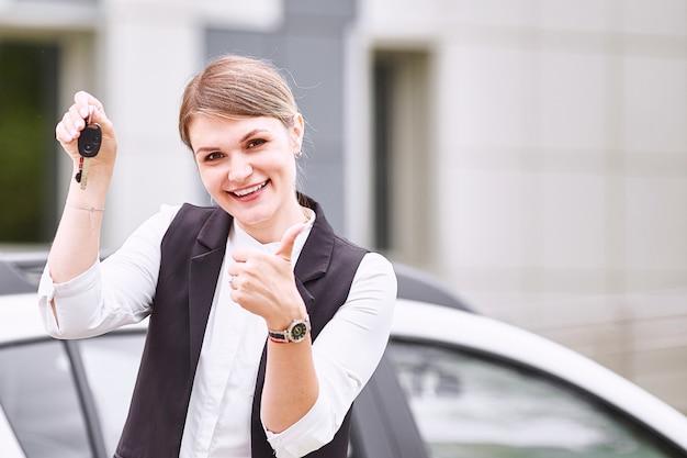 新しい車の自動キーを押しながらカメラに笑顔の女性 Premium写真