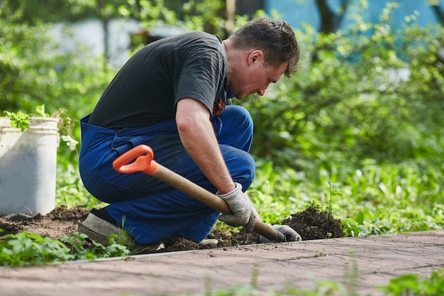 庭師は庭で春に地面を掘る。園芸。 Premium写真