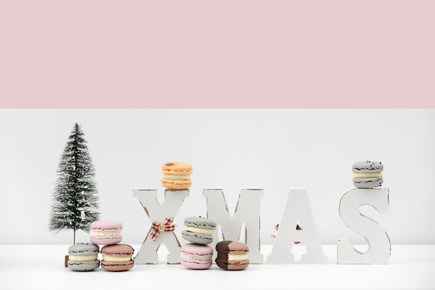 碑文のクリスマスとクリスマスの白とピンクの背景にデザートマカロンやマカロンをレンチします。食品レシピコンセプト。コピースペース。 Premium写真