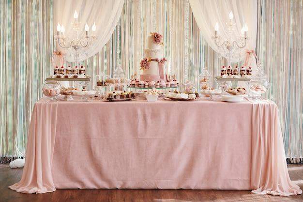 キャンディバーとウェディングケーキ。お菓子のテーブル、カップケーキのビュッフェ、キャンディー、デザート。 Premium写真
