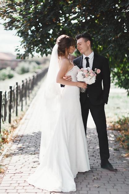 公園での結婚式のカップル。スタイリッシュで美しい豪華な白いドレスの花嫁と手にベールとブーケ。黒のスーツの新郎。 Premium写真