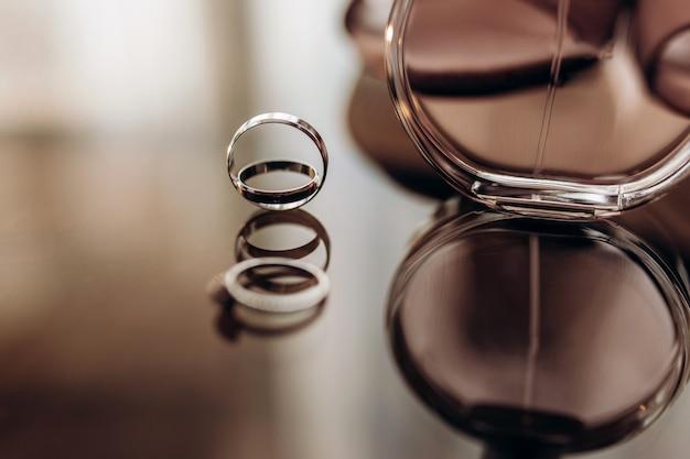 Закройте вверх по обручальным золотым кольцам с духами на стеклянном столе. подготовка к свадьбе. Premium Фотографии