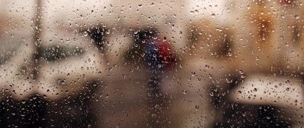 ウィンドウに雨のしずくバナー。雨の水滴がガラスを流れ落ちます。雨、しずく、雨、水滴。 Premium写真