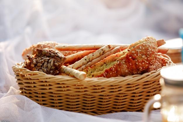 パンと籐のバスケット。バスケット内のパン、パン、グリッシーニ。ピクニックに新鮮なベーカリー製品。セレクティブフォーカス Premium写真