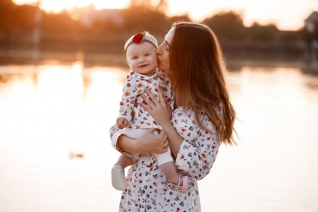 夕日に湖の近くの彼女の小さな娘にキスのママ。夏休みのコンセプトです。母の日、赤ちゃんの日。自然に一緒に時間を過ごす家族。家族の一見。セレクティブフォーカス Premium写真