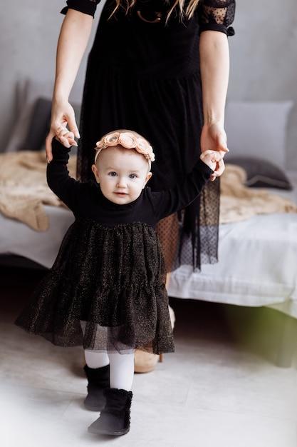 母は娘が家で一緒に時間を楽しむ手を保持しています。足を下に見ます。母の日、赤ちゃんの日。若い家族の休日のコンセプトと愛のケアと次世代へのサポート。 Premium写真
